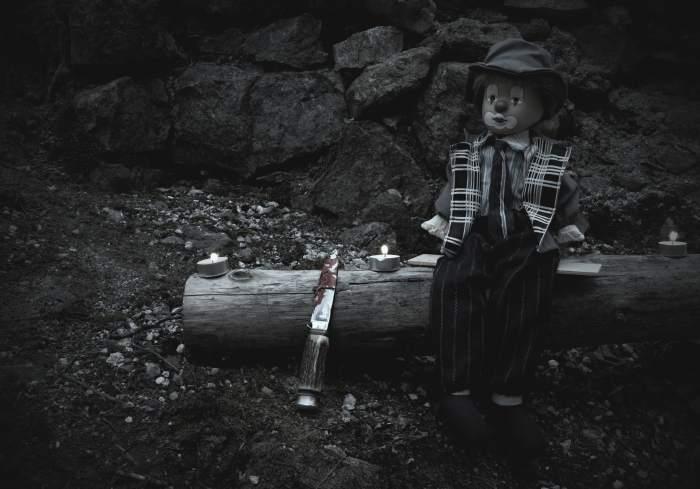 Dunkles Bild einer Horror-Clown-Puppe, die auf einem Holz in einer Burgruine wartet - schwarzweiss