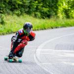 Downhill-Longboarder rotes Motorradkombi und -Helm