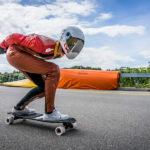 Downhill-Longboarder vor Hochspannungsleitungen in Mühleberg (Bern)